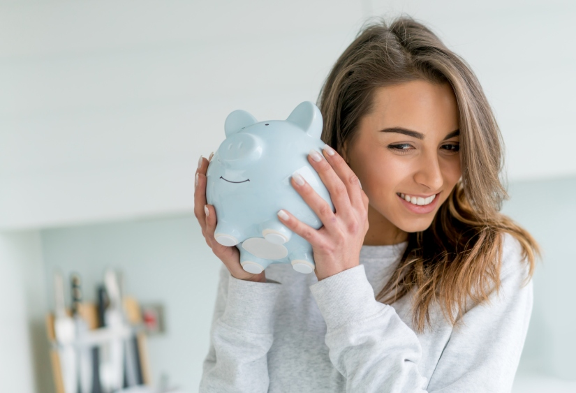 Happy woman saving money in a piggybank