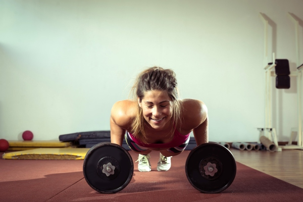 Girl doing push ups with dumbbell indoors